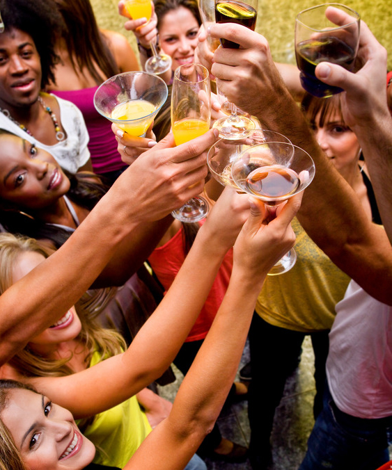Group of happy friends at a bar or a nightclub toasting
